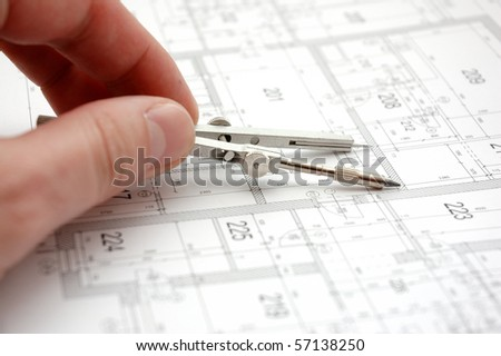 Hand with trammel on building drawing - stock photo