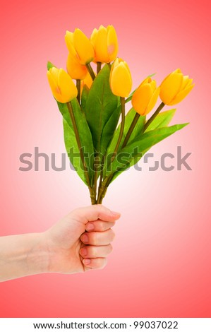 Hand with tulips on gradient