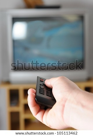 Hand with TV remote controller change the TV channel.