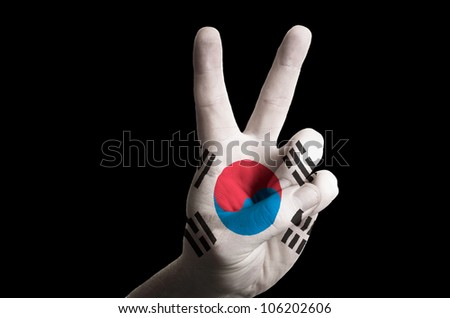Hand with two finger up gesture in colored south korea national flag as symbol of winning,  - for tourism and touristic advertising, positive political, cultural, social management of country - stock photo