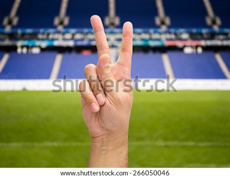 hand with two fingers concept of victory on the stadium - stock photo