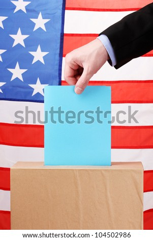 Hand with voting ballot and box on Flag of USA - stock photo