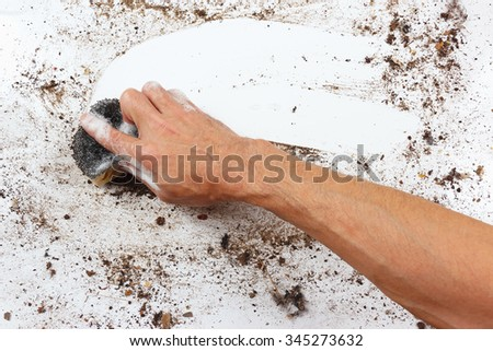 Hand with wet sponge wiping a dirty surface