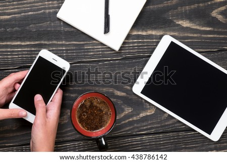 Hand with white phone, black and red cup of coffee, white tablet, white notepad with black pen on the aged wooden dark background - stock photo