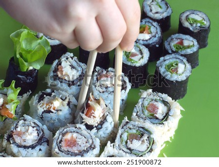 Hand with wooden chopsticks takes portion of sushi roll from row. Diagonal view closeup - stock photo