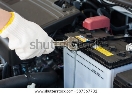 Hand with wrench repairing and checking car engine