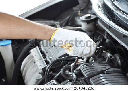 Hand with wrench repairing car engine - stock photo