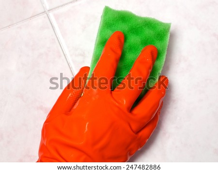 Hand with yellow sponge cleaning the bathroom tiles - stock photo