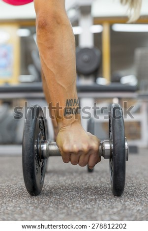 hand woman with a dumbell on the gym's floor.No pain no gain tattoo. - stock photo