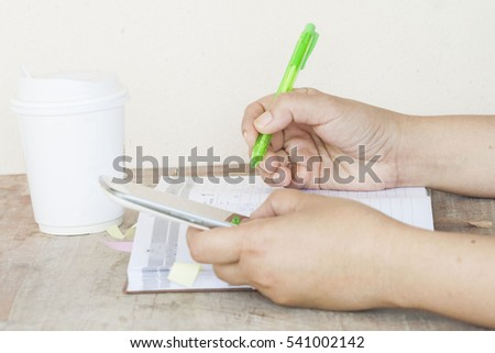 hand working financial and holding mobile on table