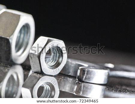 Hand wrench and metal nuts - stock photo