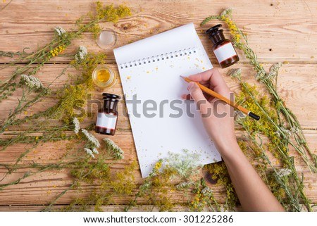 hand write a recipe in notepad on wooden table, herbs around - stock photo