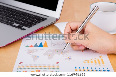 Hand write on financial chart on the table with laptop and coffee - stock photo