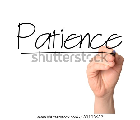 hand writes the word Patience on the whiteboard with a marker  - stock photo