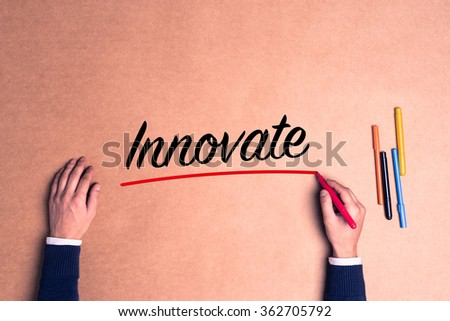 Hand writing a single word Innovate on paper - stock photo