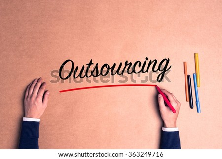 Hand writing a single word Outsourcing on paper - stock photo