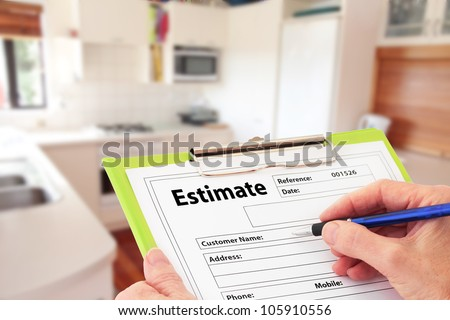 Hand writing an estimate on a clipboard to renovate a kitchen - stock photo