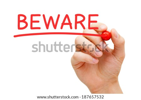 Hand writing Beware with marker on transparent wipe board. - stock photo