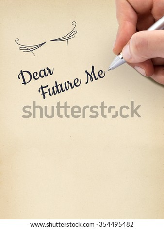 """Hand writing """"Dear Future Me"""" on aged sheet of paper. - stock photo"""