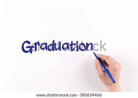 Hand writing GRADUATION on white paper, View from above - stock photo