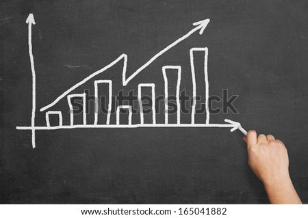 Hand writing graph on blackboard - stock photo
