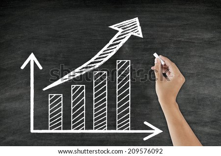 hand writing growing graph and arrow on blackboard