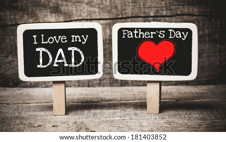 Hand writing I Love Dad and Father's Day on two chalkboards on wood background - stock photo