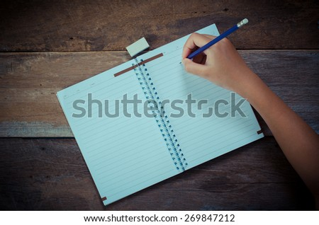 Hand writing in open notebook on table - hand focus  - stock photo