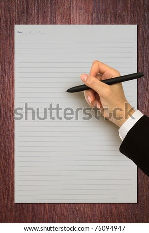 Hand writing in open paper on table - stock photo