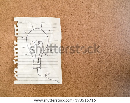 Hand writing light bulb on crumpled paper on brown background -business concept idea and strategy - stock photo