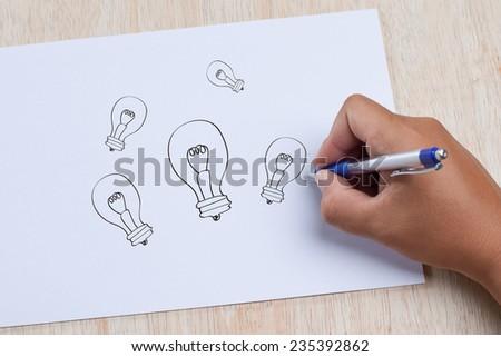Hand writing Light bulb on paper - stock photo
