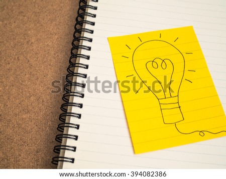 Hand writing light bulb on yellow paper on brown background -business concept idea and strategy - stock photo