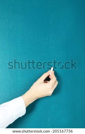 Hand writing on blackboard in class room - stock photo