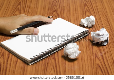 hand writing on notebook with crumpled paper on wood table background - stock photo