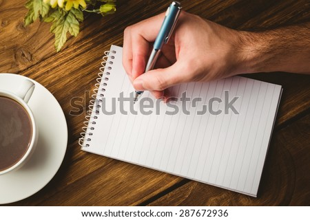 Hand writing on the notepad on a desk - stock photo
