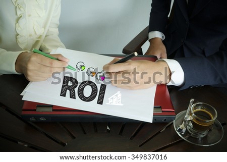 hand writing ROI text with two business person , team work concept - stock photo