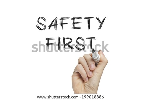 Hand writing safety first on a white board - stock photo