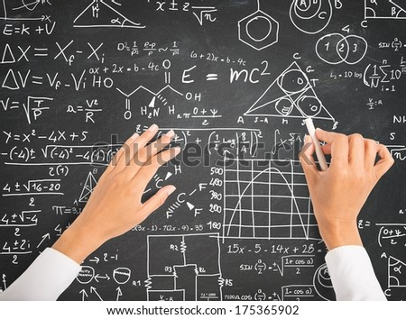 Hand writing science and math formulas on chalkboard - stock photo