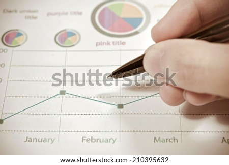 Hand writing something on the paper on the foreground. - stock photo