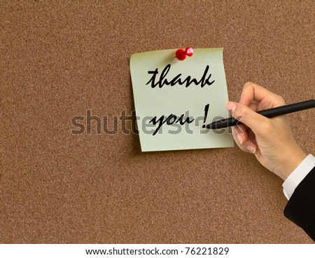 """Hand writing """" thank you """" in paper note on cork board background - stock photo"""