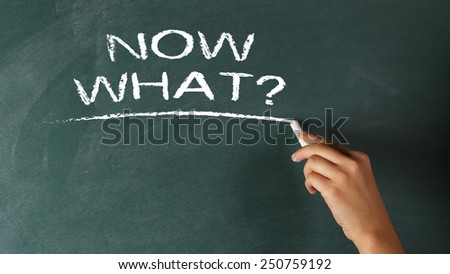 Hand writing The question Now What? on a blackboard