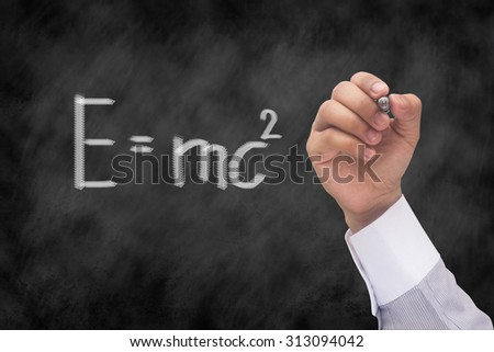 hand writing the Theory of relativity by Albert Einsteins over chalk board background textures. - stock photo