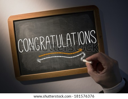 Hand writing the word congratulations on black chalkboard - stock photo