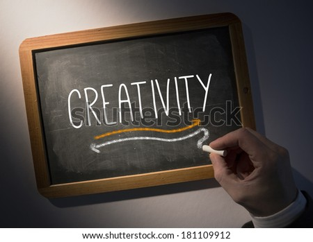 Hand writing the word creativity on black chalkboard