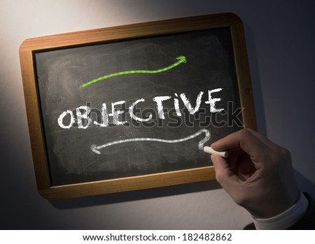 Hand writing the word objective on black chalkboard