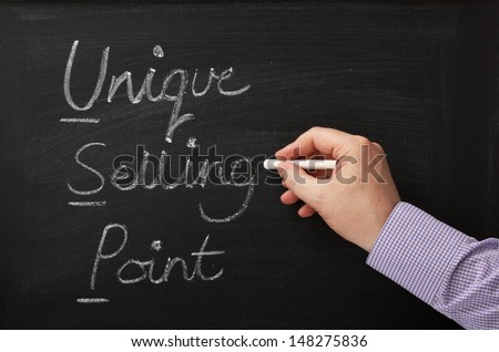 Hand writing the words Unique Selling Point on a blackboard. The USP of your business plan is a key to success and competitive advantage in the market place - stock photo