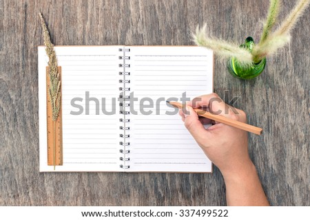 Hand Writing with Pencil on Blank Notebook on Wooden Table Background in Business Concept