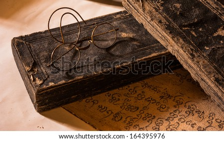 Hand Written Ancient Treatise of Lanna character with very old glasses retro style - stock photo