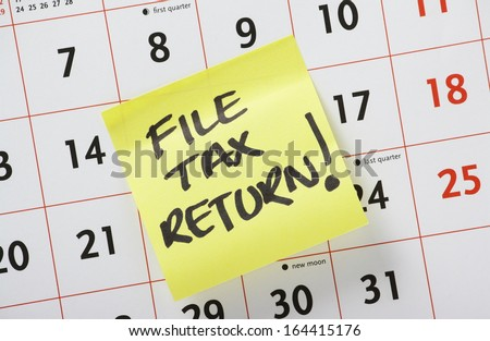 Hand written reminder to File Tax Return on a yellow post it note stuck to a calendar background - stock photo