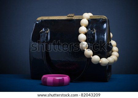 Handbag and jewelry on a dark background